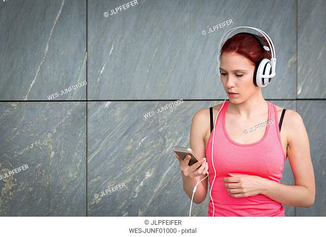Woman in sports outfit wearing headphones, listening music