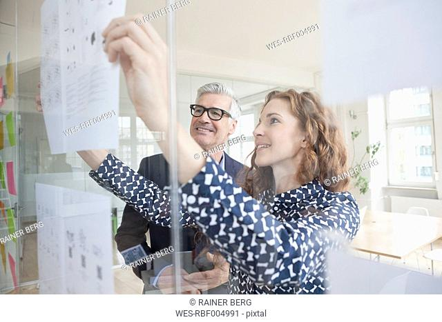 Businessman and woman looking at paper at glass pane