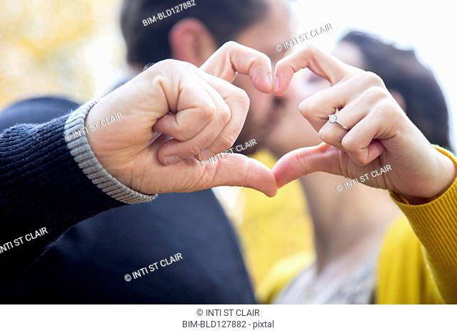 Caucasian couple making heart shape with fingers