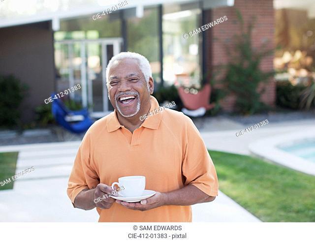 Older man having cup of coffee in backyard