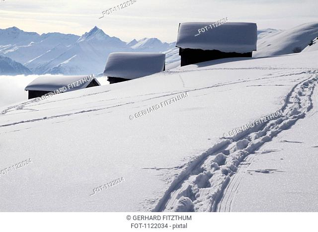 Foot path leading to three snow-capped log cabins