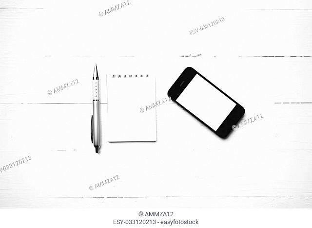 cellphone with notepad and pen over white table black and white color style