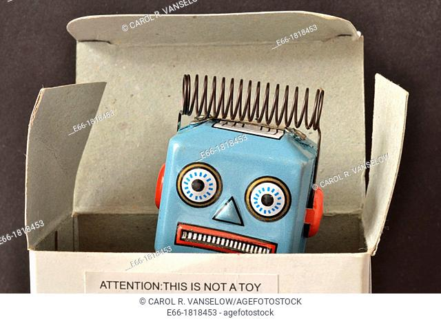 light blue wind-up robot, showing head with electrical coil peaking out of box with notice on box saying: 'Attention: This is not a toy '