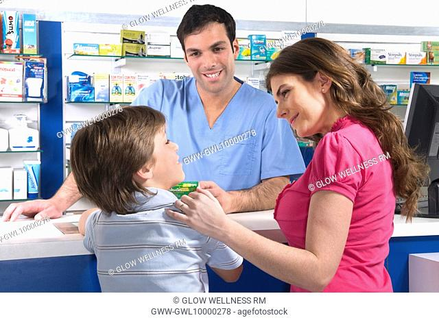 Pharmacist looking at boy standing with his mother
