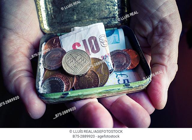 Woman's hands holding a metal box full of coins and banknotes (pounds sterling), England