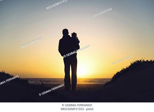 USA, California, Morro Bay, silhouettes of father and baby enjoying sunset on the beach