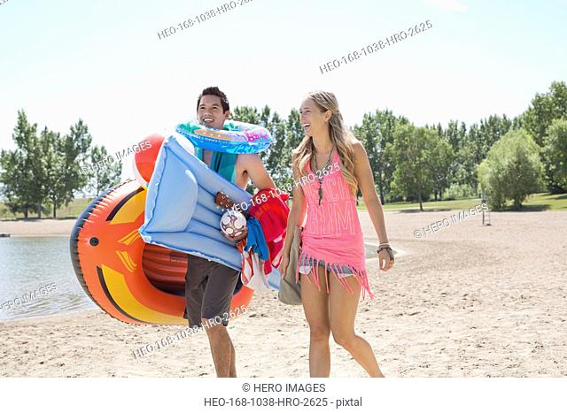 Couple walking on beach with inflatable rafts