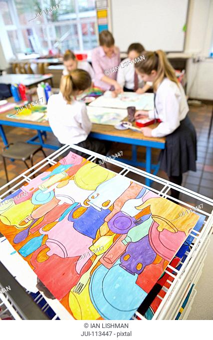 Painting drying with art teacher teaching middle school students in art class