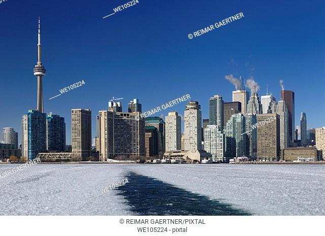 Wake of a winter ferry to the Toronto Islands with city skyline and ice slush