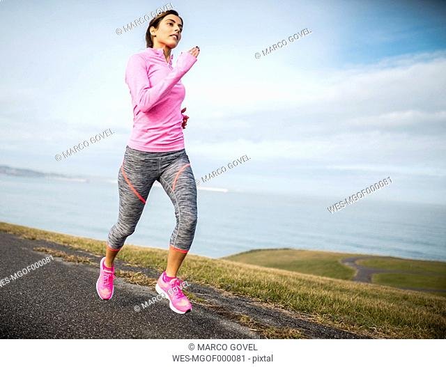 Spain, Gijon, sportive young woman running on path at the coast