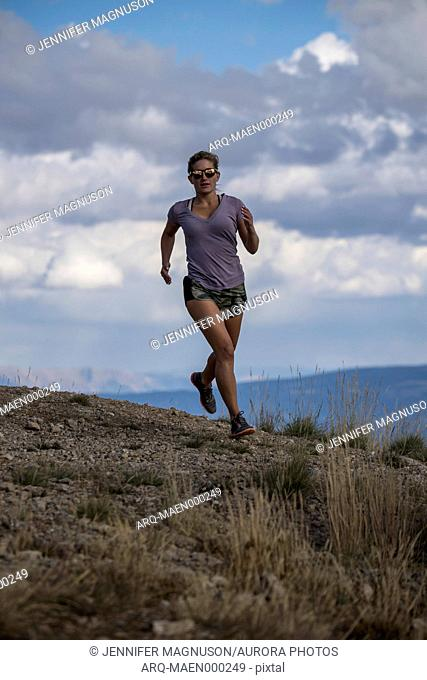 Female trail runner with mountains in background, Jackson Hole, Wyoming, USA