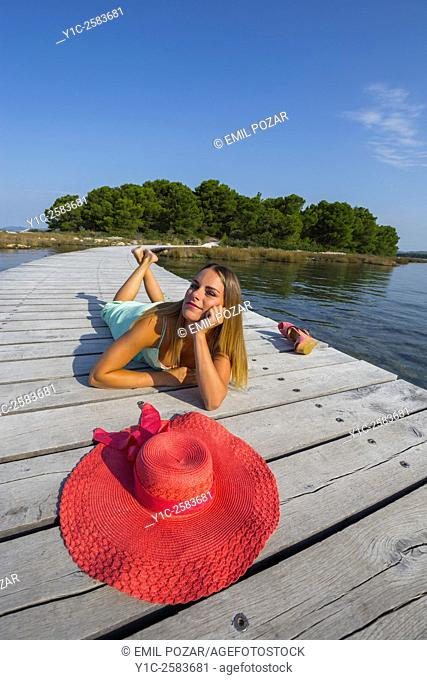 Attractive young woman and wide Red hat in foreground