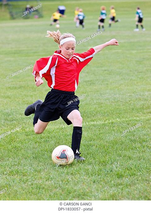 Female soccer player kicking the ball