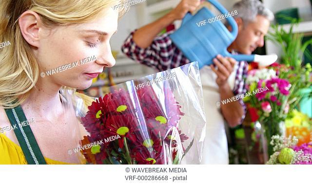 Beautiful female florist smelling bouquet of flower