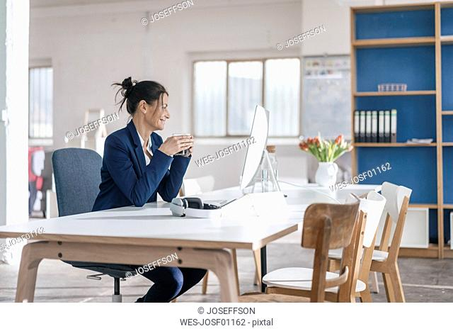 Businesswoman sitting at desk in a loft drinking coffee