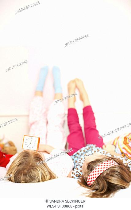 Back view of two little girls lying on bed looking at alarm clock