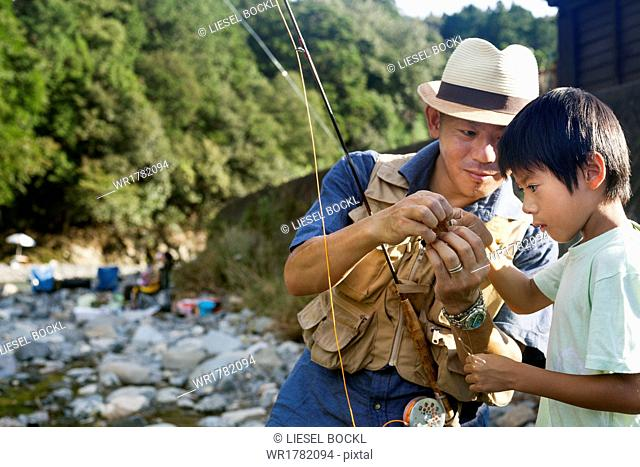Father and son fishing by a stream