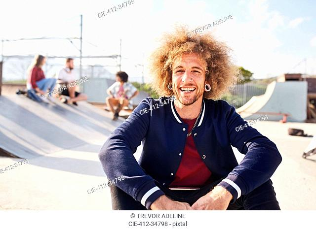Portrait confident young man with afro at sunny skate park