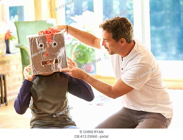 Father placing robot mask on son