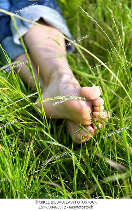 legs of a young barefooted woman resting on a peaceful field of grass