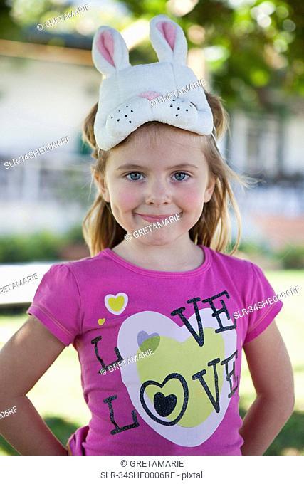 Girl wearing rabbit mask outdoors