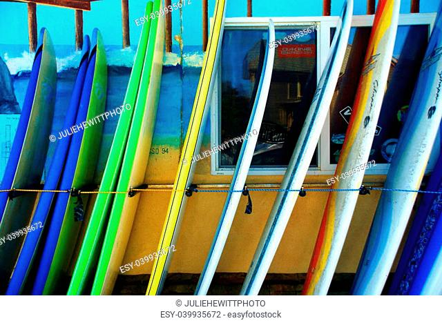 Colorful blue, green, and yellow surfboards on the dock at Pismo Beach, CA standing vertically in front of surfing shop awaiting tourists and sportsmen in the...