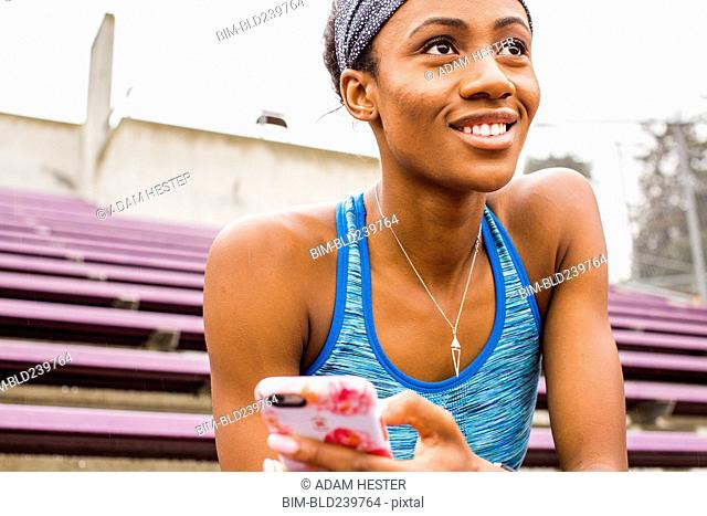 Smiling Black woman sitting on bleachers texting on cell phone