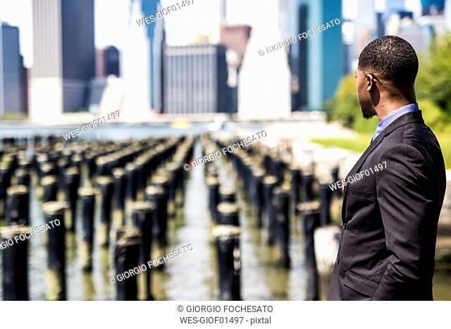 USA, Brooklyn, businessman looking at Manhattan