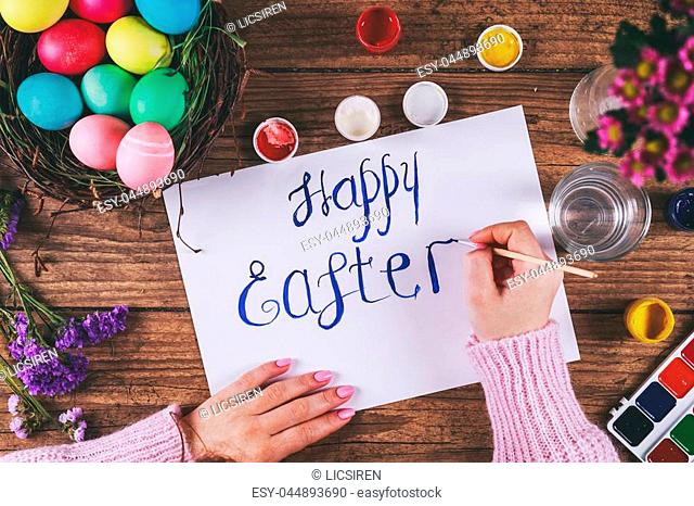 Hand with brush writing Happy Easter. Toned picture. Top view. Selective focus