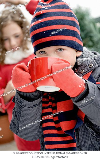Boy wearing winter clothes drinking from a large cup