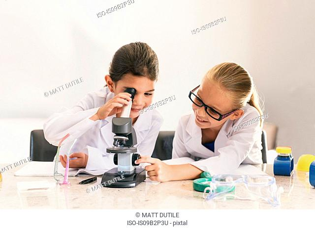 Girls wearing lab coats using microscope
