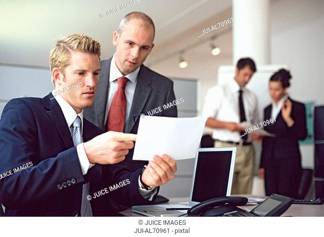 View of two businessmen discussing a memo
