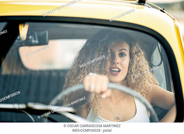 Portrait of surprised blond woman driving classic car