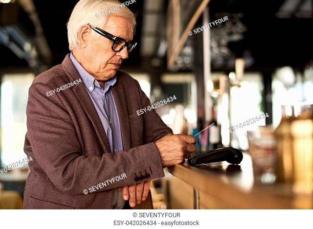 Side view portrait of modern senior man paying via contactless bank card in cafe