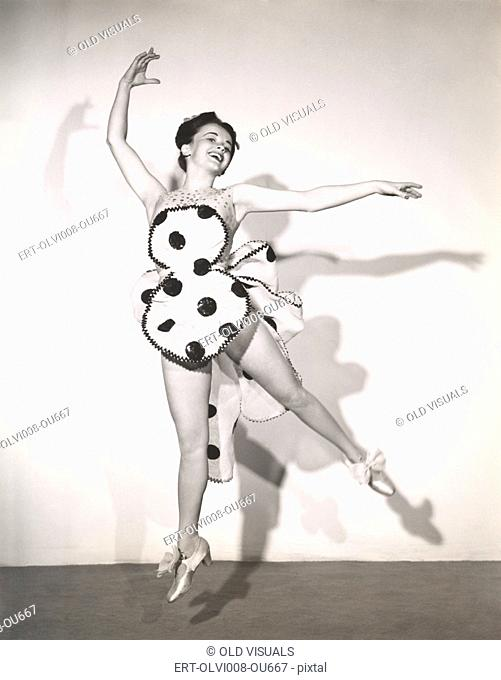Dancer in polka dot costume leaping in mid air