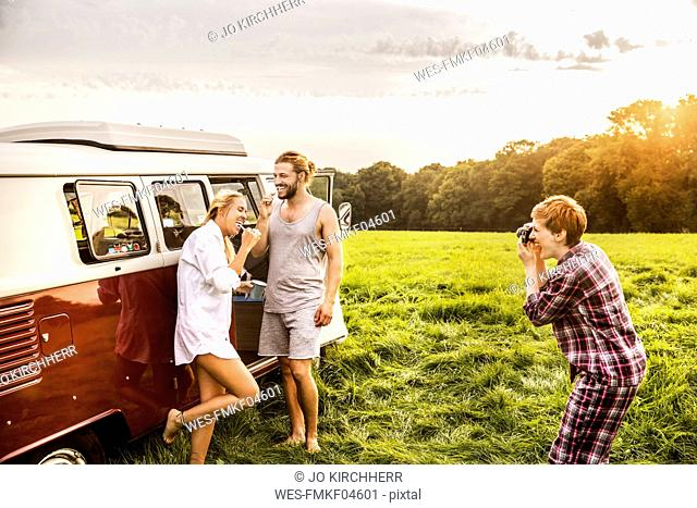 Woman taking picture of friends brushing teeth at a van in rural landscape