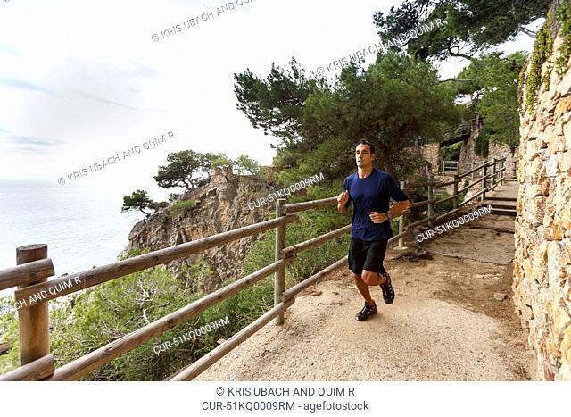 Man running on rocky coastline