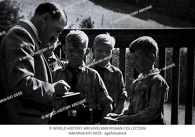 Adolf Hitler 1889-1945. German politician and the leader of the Nazi Party greets Hitler youth boys