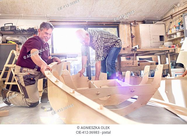 Male carpenters making wood boat in workshop