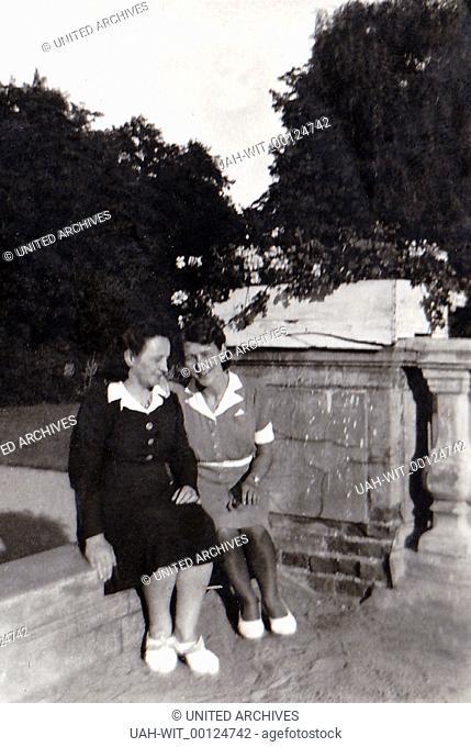 Zwei Frauen sitzen im Park am Sockel eines Denkmals., Sammlung Wittmann