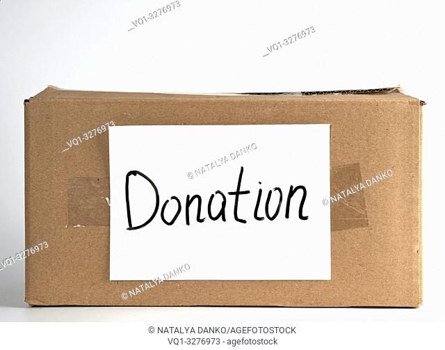 closed brown cardboard box with the inscription donation , white background