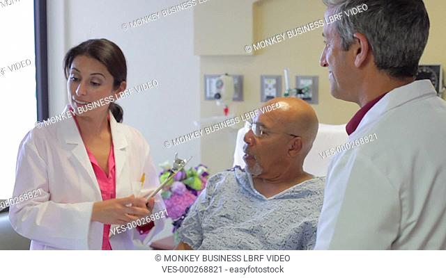 Medical team meeting around senior male patient in hospital bed to discuss case.Shot on Sony FS700 in PAL format at a frame rate of 25fps
