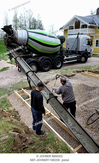 Two men working with concrete mixer truck