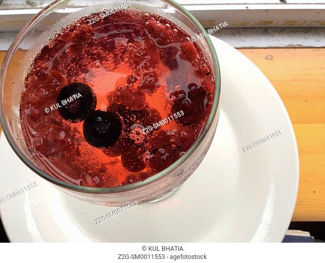 Berries float in a rose coloured drink with bubbles, Nova Scotia Canada