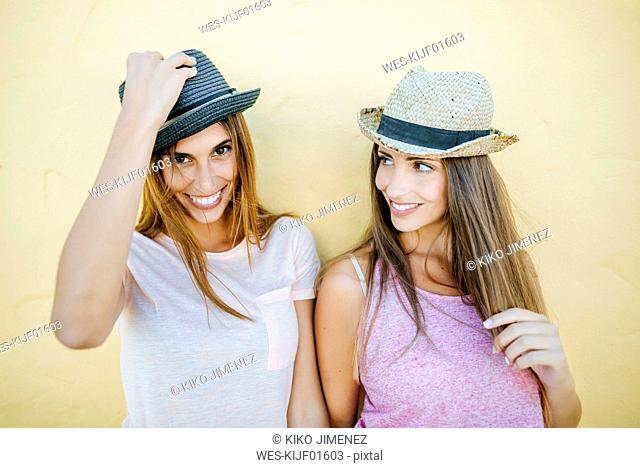 Portrait of two smiling women wearing hats