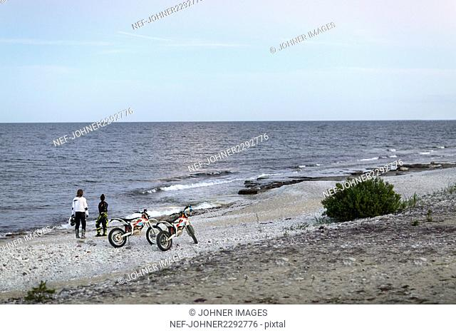 Couple standing next to their motorbikes on beach