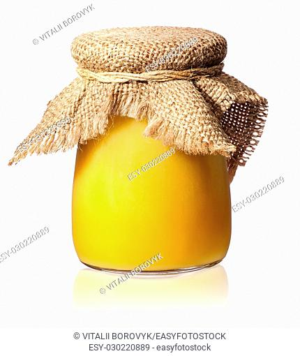 Honey in a glass jar covered with burlap isolated on white background
