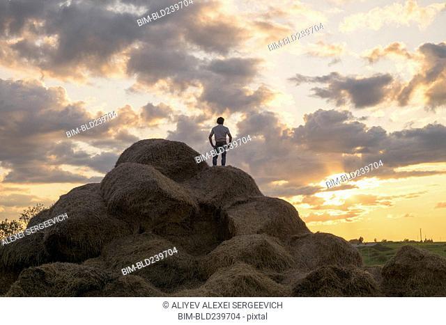 Caucasian man standing on rock pile at sunset