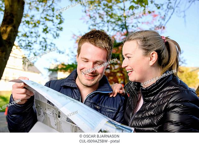 Young couple looking at map, downtown, Torshavn, Faroe Islands