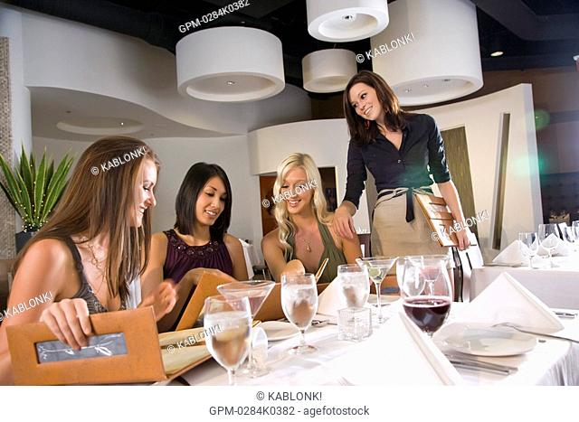 Portrait of young happy women sitting at a table in upscale restaurant